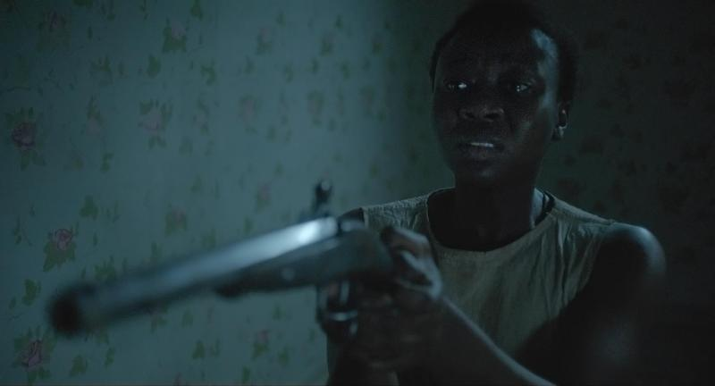 Keeping_Room-Gun: Mad (Muna Otaru) prepares herself to defend against an intruder in Drafthouse Films' The Keeping Room. Courtesy of Drafthouse Films.