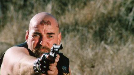 -Dangerous_Men-Taking-Aim: The burly head biker (Tom Shelorke) takes aim in Drafthouse Films' Dangerous Men. Courtesy of Drafthouse Films.