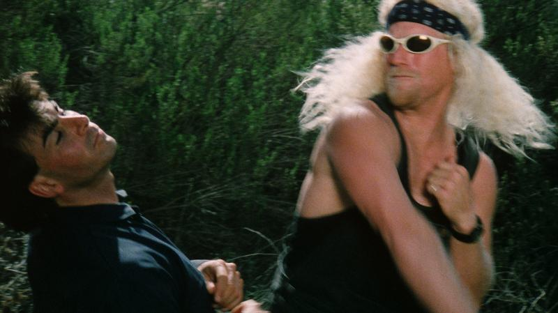 Dangerous_Men-Black-Pepper-Punch: The villainous crimelord Black Pepper (Bryan Jenkins) punches David (Kelay Miller) in the face in Drafthouse Films' Dangerous Men. Courtesy of Drafthouse Films.