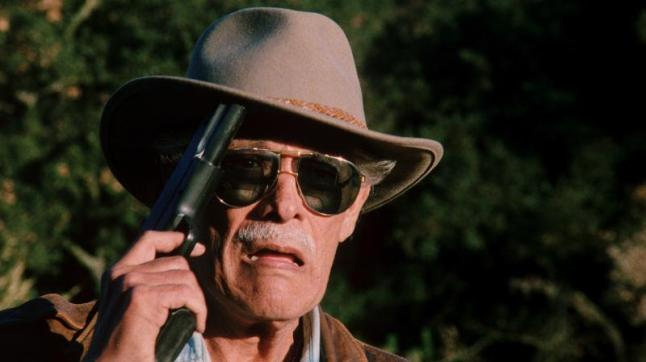 Dangerous_Men-Holy-Shit: The chief (Carlos Rivas) incredulously observes a brutal fistfight from the distance in Drafthouse Films' Dangerous Men. Courtesy of Drafthouse Films.