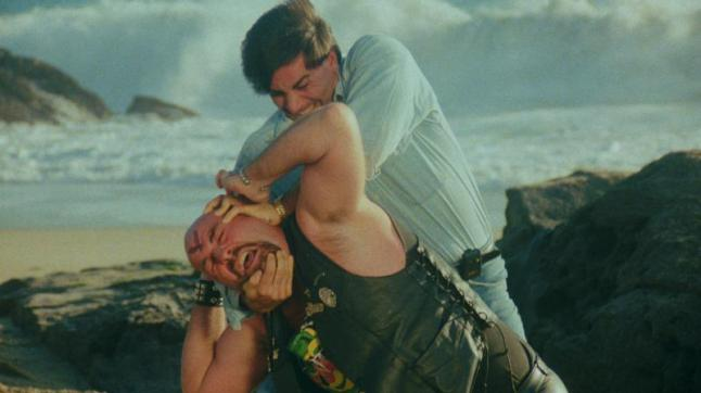 Dangerous_Men-Headlock: The heroic David (Kelay Miller) holds the head biker (Tom Shelorke) in a headlock in Drafthouse Films' Dangerous Men. Courtesy of Drafthouse Films.